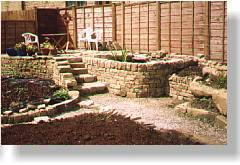 Raised patio and pond, steps, boulders and use of vertical stones as path edges in this new garden; the hard landscaping being part of a design by Jane Hurford