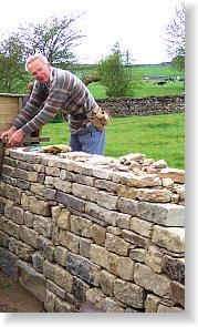 John Heslegrave removing the walling frame before adding cope stones to the first stint of this new part-retaining garden wall.		Photo by Philip Wolstenholme
